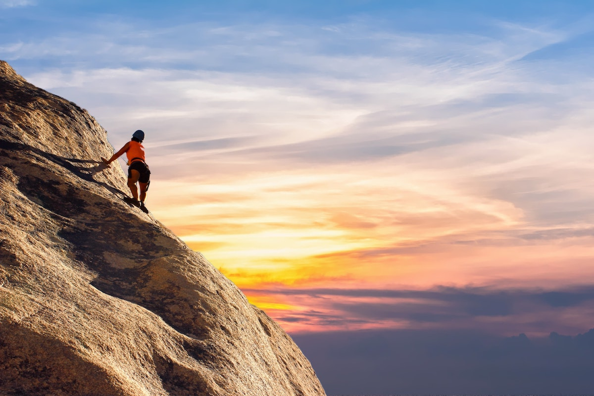 photo of rock climber scaling a rock at sunrise
